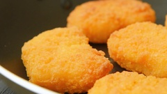 Cooked chicken nuggets in black frying-pan Stock Footage