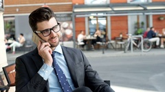 Handsome businessman sitting in the outdoor cafe and talking on cellphone Stock Footage