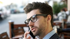 Handsome businessman with glasses talking on cellphone in the outdoor cafe Stock Footage