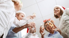 Cheerful colleagues rising their glasses for toast Office party Shot from below Stock Footage