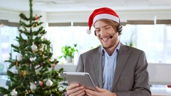 Handsome cheerful young businessman wearing christmas hat holding tablet having Stock Footage