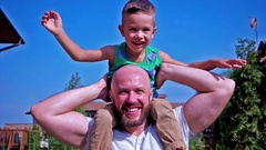Portrait of the son and the father, child sitting on the shoulders of his dad Stock Footage