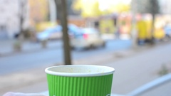 Paper cup with fragrant citrus tea is on the table. The man takes it, takes a si Stock Footage