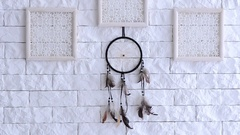 Dreamcatcher hanging on a white brick wall between the wooden frames. Feathers s Stock Footage