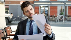Occupied businessman working on outcomes while sitting outdoors, steadycam shot Stock Footage