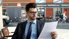Businessman looking absorbed while reading papers, steadycam shot Stock Footage