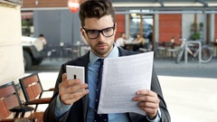 Businessman checking outcomes on papers and smartphone, steadycam shot Stock Footage