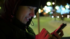 Man sms texting using app on smartphone at night in city, winter time. closeup Stock Footage