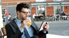 Businessman drinking orange juice while browsing internet on tablet Stock Footage