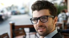 Handsome businessman wearing glasses and talking to someone Stock Footage