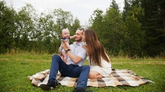 Happy family parents playing with baby during picnic in park Stock Footage