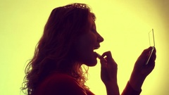 Near silhouette of a young woman applying lipstick. Stock Footage