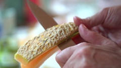 Woman hands cutting cantaloupe melon with a knife Stock Footage