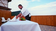 Cook at home, Professional chef serves a table on the terrace, a table covered Stock Footage