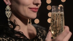Woman drinking champagne from a glass on a background of celebratory lights at Stock Footage