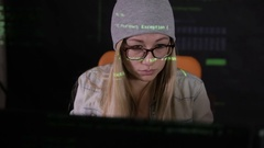 Serious young woman using computer at night in dark room. Computer code Arkistovideo