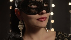 Woman in a Venetian mask on the background of night lights, close-up Stock Footage