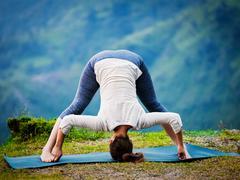 Woman doing Ashtanga Vinyasa Yoga asana Prasarita padottanasana Stock Photos