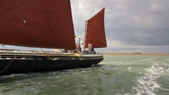 Tracking shot along side of Thames sailing barge at sea Stock Footage