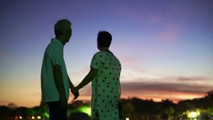 Asian senior couple silhouette with early morning sky and moon background Stock Footage