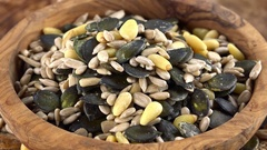 Mixed Seeds rotating on a wooden plate (not loopable; 4K) Stock Footage