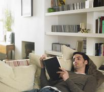 Man Lying Down on Sofa Reading Book Stock Photos