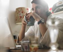Portrait of Man Sitting in Front of Laptop Computer, Holding Mug Stock Photos
