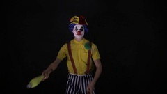 Terrible horror clown. Scary mad Juggler clown using juggling pins Stock Footage