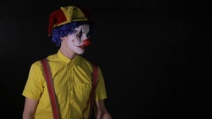 Scary juggler clown juggling axe in a dark room. Frightening jester, clown Stock Footage