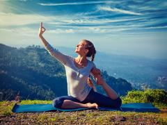 Sorty fit woman doing yoga asana outdoors in mountains Stock Photos