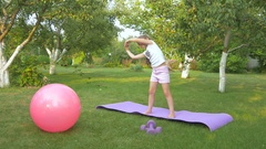 The little girl doing physical exercises in garden Stock Footage
