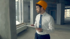 Investor inspecting building. Businessman in hard hat inside construction site Stock Footage
