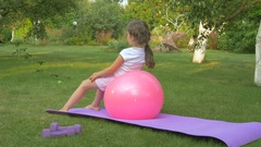 The girl doing exercises with ball in garden Stock Footage