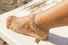 leg of a young girl and anklet ankle Stock Photos