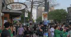 People walk along 6th street by 512 club sign during SXSW festival Austin,TX 4K Stock Footage