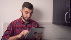 Attractive Young Man Use Tablet in Kitchen Stock Footage