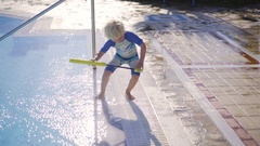 Boy Filling And Spraying With Water Gun On Poolside Stock Footage