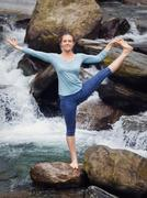 Woman doing Ashtanga Vinyasa Yoga asana outdoors at waterfall Stock Photos