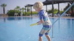 Boy Shooting With Watergun On Poolside At Resort Stock Footage