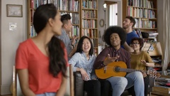 4K Portrait happy young woman in shared apartment with fiends playing guitar Stock Footage
