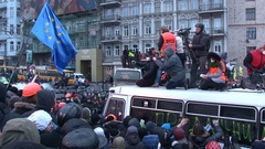 Journalists with cameras standing on the broken bus among the protesting crowd. Stock Footage