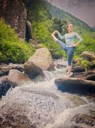 Woman doing Ashtanga Vinyasa Yoga asana outdoors at waterfall Stock Photos