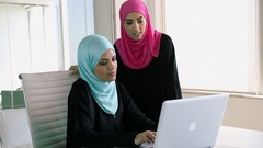 Two women working together on a laptop in the office Stock Footage