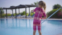 Girl Filling And Shooting Watergun On Poolside At Resort Stock Footage