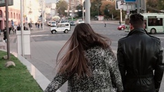 Lovers walk in the street. Handsome stylish man with a beard looks back in Stock Footage