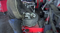Close up of mechanic inflating tire on wheel in workshop Stock Footage