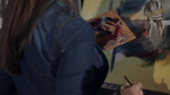A woman artist works on a painting palette knife and oil paints Stock Footage