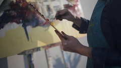 Female artist hand using a palette knife to apply paint to the canvas. close-up Stock Footage