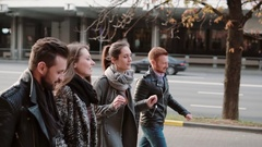 Side view of smiling people cheerfully walking near road in city centre. Friends Stock Footage