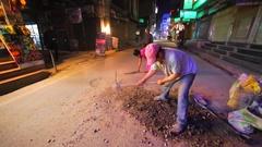 Man repairs the road, woman helps him. Evening in Thamel. Kathmandu, Nepal Stock Footage